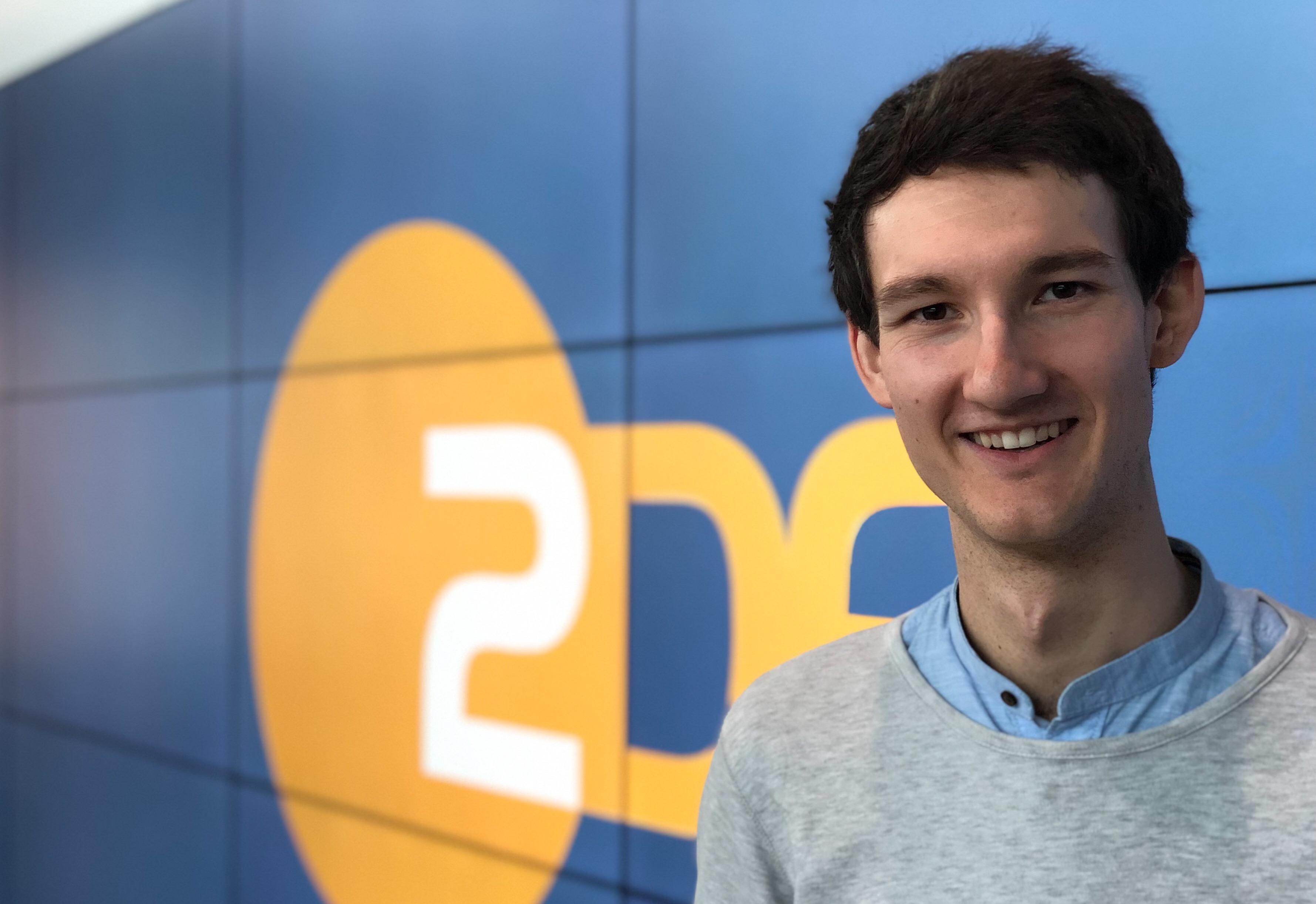 Sprecher Florian Eib vor einer Wand mit dem Logo des ZDF.