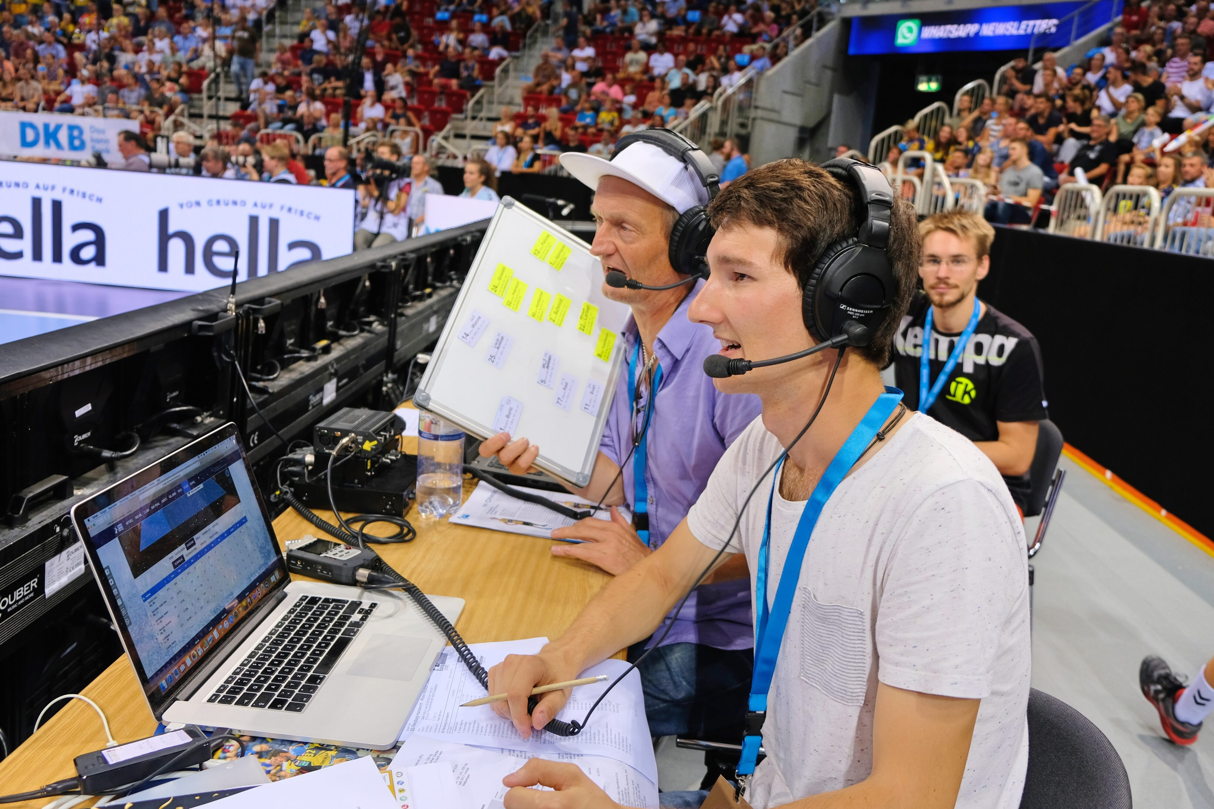 Zwei Audiodeskriptionsreporter sitzen an einem langen Tisch, jeder von ihnen hat ein Headset auf. Auf dem Tisch steht ein Laptop. Im Hintergrund viele Menschen auf in einer Halle mit steil nach oben laufenden Zuschauerrängen.