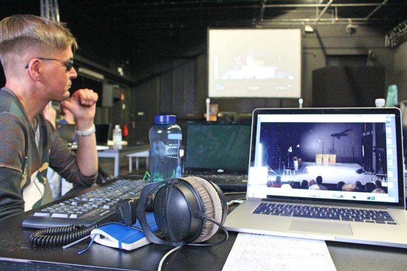 Im Vordergrund dieses Fotos sind ein Laptop mit einem Kopfhörer auf einem Tisch zu sehen, im Hintergrund eine große Leinwand auf der eine Video eines Theaterstücks projiziert ist. Links am Tisch sitzt ein Mann mit Brille.