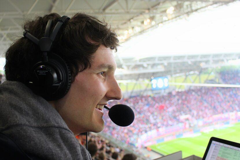 Sportreporter Florian Eib in einem gefüllten Fußballstadion. Während der Reportage lächelt er, Foto: Tomke Koop.