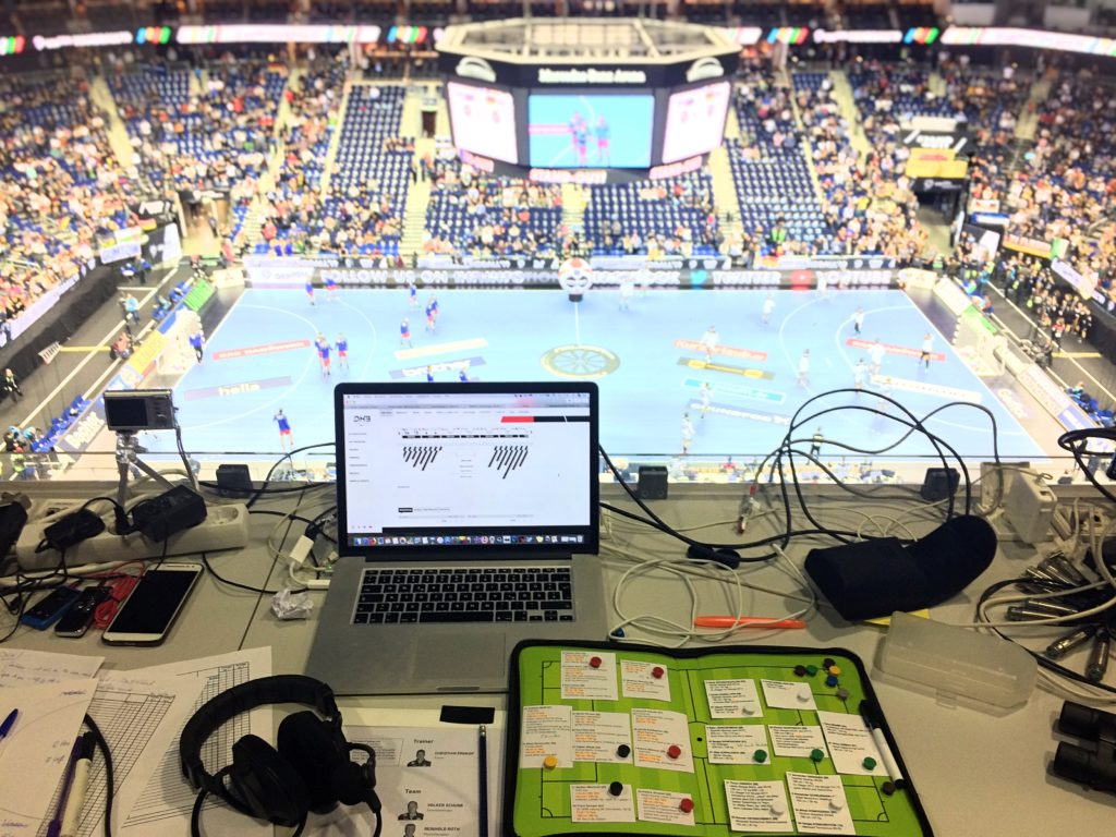 Ein Blick von hoch oben auf dem Rang in einer großen Sporthalle. Entfernt, im Hintergrund, ein Handballspielfeld mit mehreren Spielern. Im Vordergrund ein Arbeitstisch mit Laptop, Headset, zahlreichen Kabeln und einem Taktik-Board, auf dem sich viele beschriebene Zettel befinden, Foto: Florian Eib