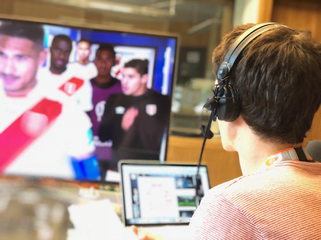 Im Vordergrund, mit dem Rücken zum Fotograf sitzt Florian Eib (Sprecher für Audiodeskription) in einem Studio. Er hat ein Headset auf. Etwas verschwommen im Hintergrund ist ein großer Bildschirm zu sehen, auf welchem eine Fußballmannschaft in rot-weißen Trikots durch einen Spielertunnel läuft, Foto: Johannes Karner.