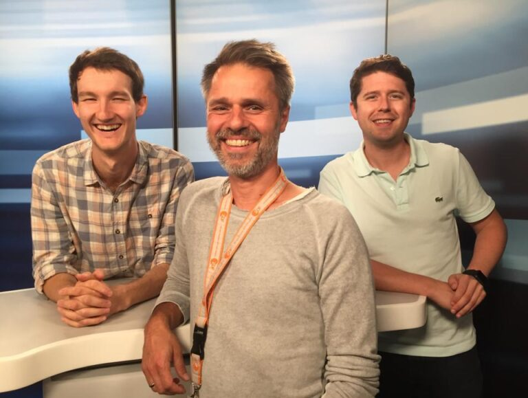 Die Sprecher für Audiodeskription Florian Eib, Martin Feye und Johannes Karner (von links nach rechts) stehen an einem Moderationstisch. Sie grinsen in die Kamera, Foto: H. Anuschek.