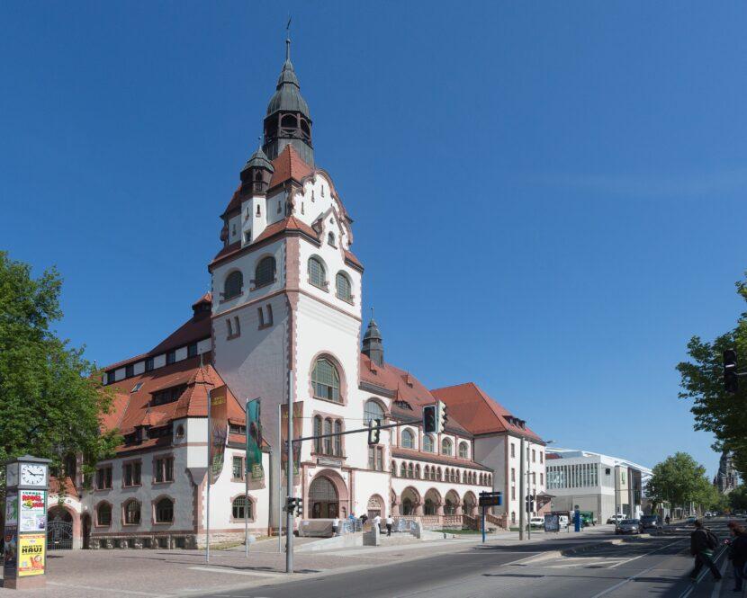 Der große Turm der Kongresshalle ragt in den blauen sommerlichen Himmel. Rechts vom Turm weg erstreckt sich in einem Flachbau die Kongresshalle am Zoo Leipzig.
