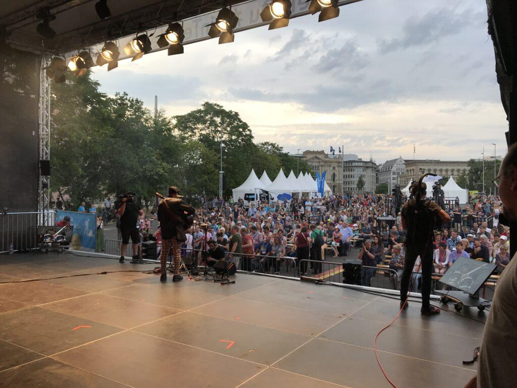 Blick von einer großen Bühne auf etwa 2.500 Menschen, die teilweise sitzend und teilweise stehend einem Bühnenprogramm folgen. Im Hintergrund sind einige Gebäude der Leipziger Innenstadt zu sehen.