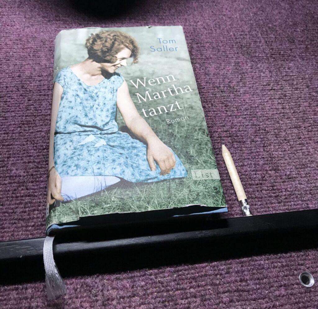 Eine Fotografie des Buches, auf welchem eine junge Frau mit einem blauen Kleid abgebildet ist. Sie lächelt verschmitzt, ihre halblangen roten Haare sind lockig.