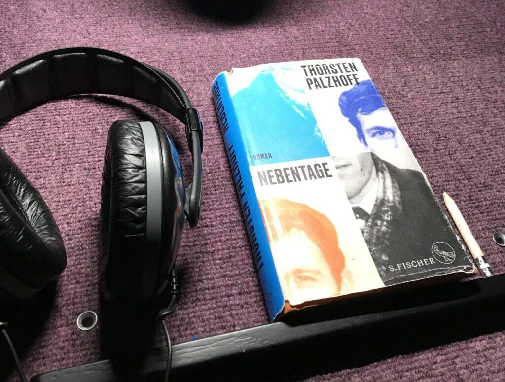 Auf einem Schreibtisch liegt das Buch Nebentage, daneben ein Kopfhörer. Auf dem Cover des Buches sind Teile einer männlichen Silhouette verkehrt herum angeordnet.