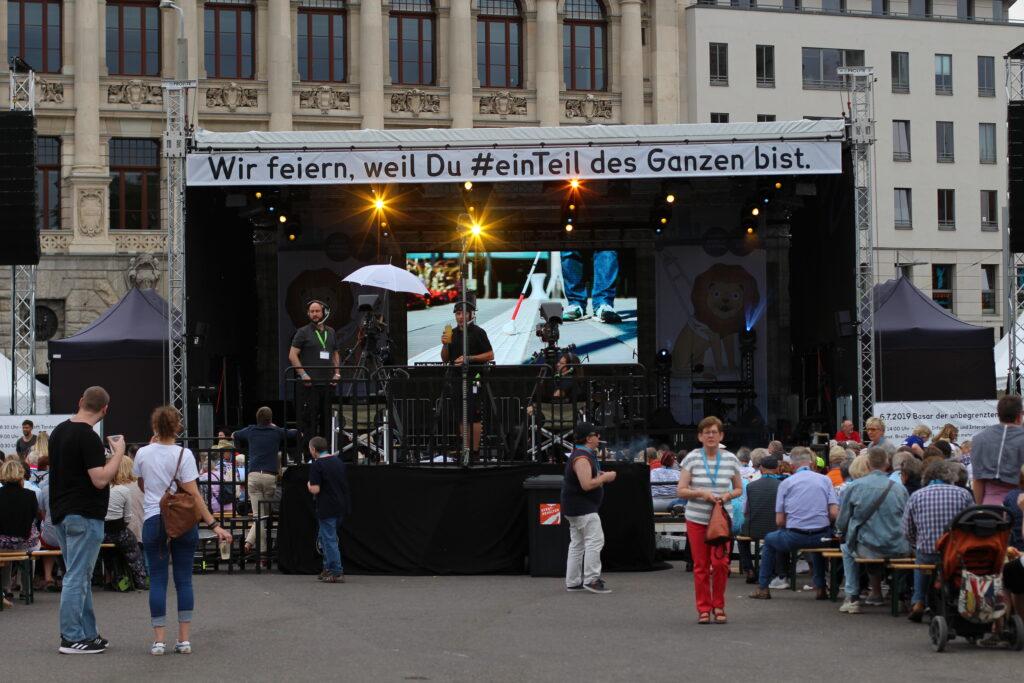 """Eine Bühne auf dem Wilhelm-Leuschner-Platz im Leipziger Zentrum. Auf einem großen Banner an der oberen Bühnenkante steht """"Wir feiern, weil du ein Teil des Ganzen bist""""."""