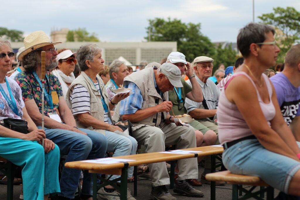 Auf Bierbänken setzen mehrere Menschen. Sie schauen zu einer großen Bühne. Einige haben einen Blindenstock dabei.