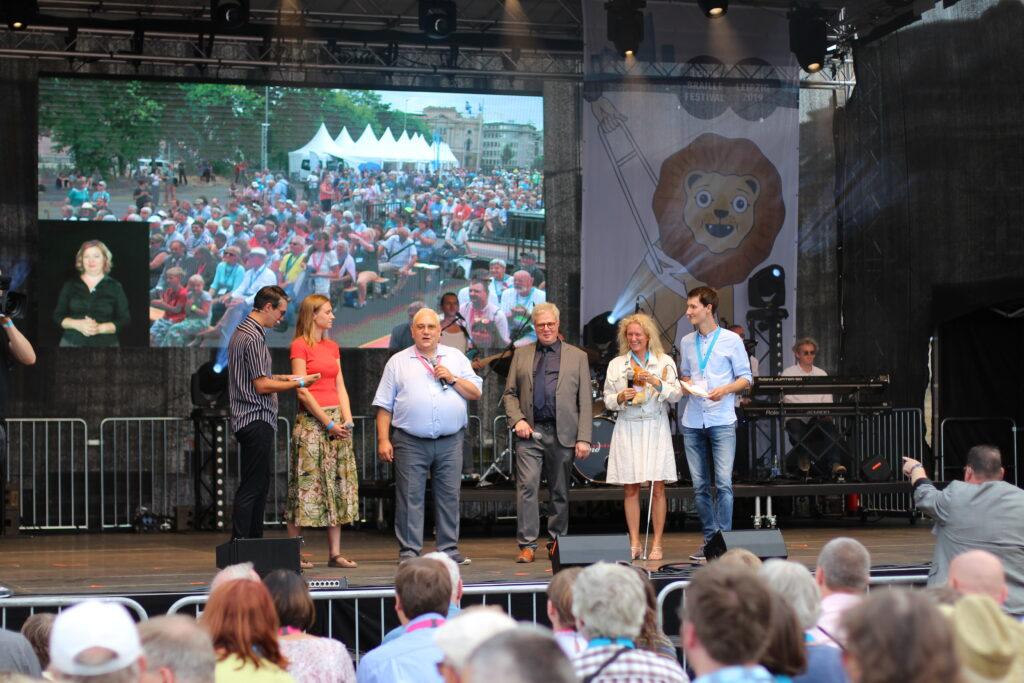 Auf einer grüßen Bühne stehen zwei Moderatoren und ihre Gäste. Im Vordergrund ist ein gut gefüllter Zuschauerbereich zu erkennen.