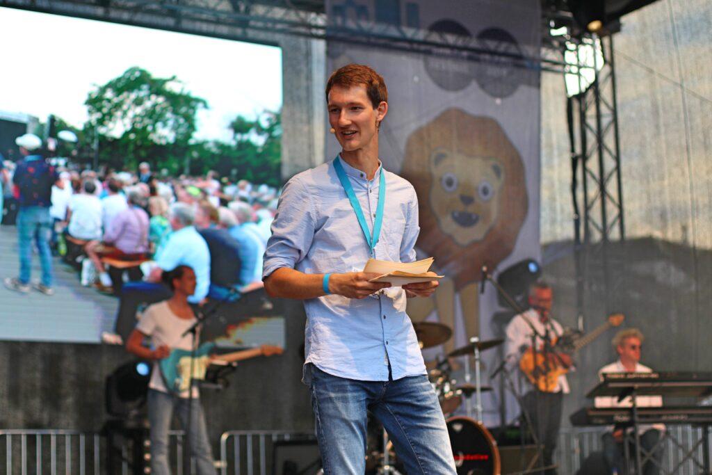 In blauem Hemd und mit Headset steht Florian Eib auf einer großen Bühne. Er hält Moderationskarten in der Hand. Im Hintergrund ist eine Showband zu sehen.