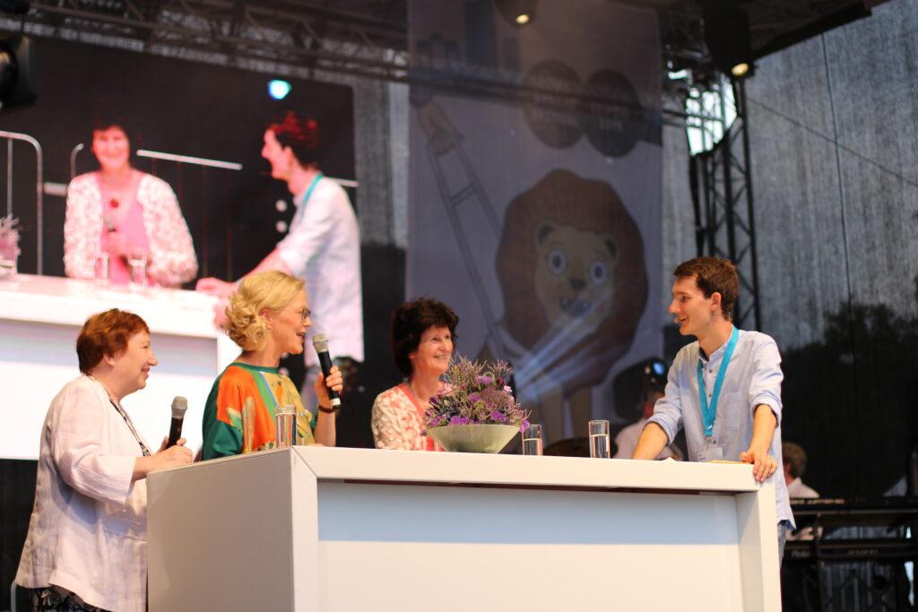An einem breiten Tisch stehen die Gesprächsteilnehmerinnen und der Moderator. Auf dem Tisch steht ein Blumenstrauß. Im Hintergrund wir das Gespräch auf einer großen Leinwand übertragen.