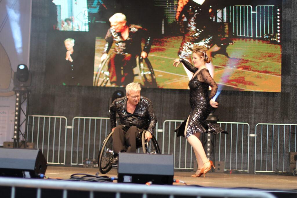 Ein Mann im Rollstuhl und eine eine Frau daneben tanzen gemeinsam. Beide sind elegant schwarz gekleidet. Sie treten auf einer großen Bühne auf während des Louis-Braille-Festivals in Leipzig auf.