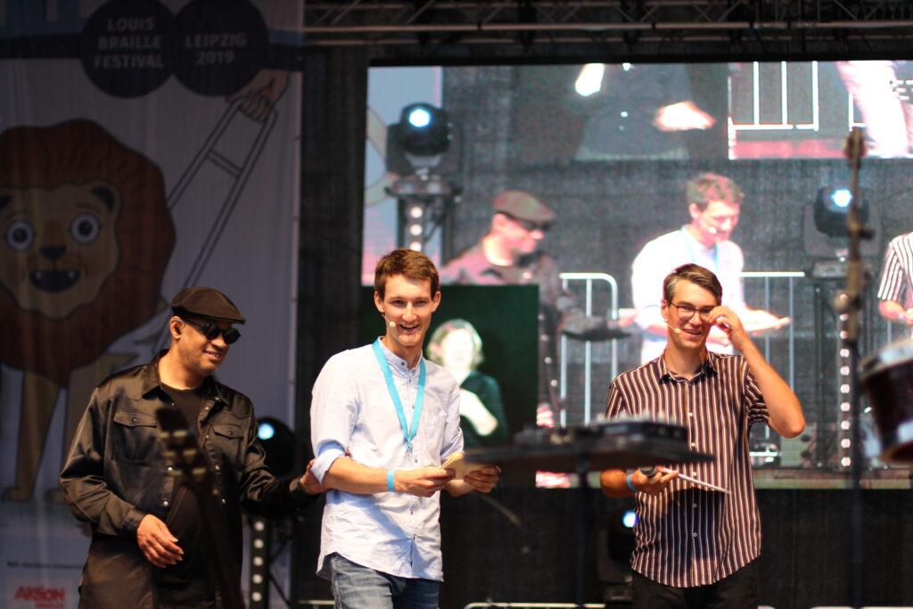 Jazz-Musiker Raul Midón und Moderator Florian Eib betreten gemeinsam die Bühne des Lousi-Braille-Festivals 2019. Florian Eib führt Raul Midón zu seinen Instrumenten.