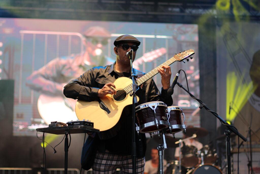 Ein blinder Musiker mit schwarzer Sonnenbrille und einer hellen Akustikgitarre steht auf einer großen Bühne. Um ihn herum stehen Bongos, er singt in ein Mikrofon.