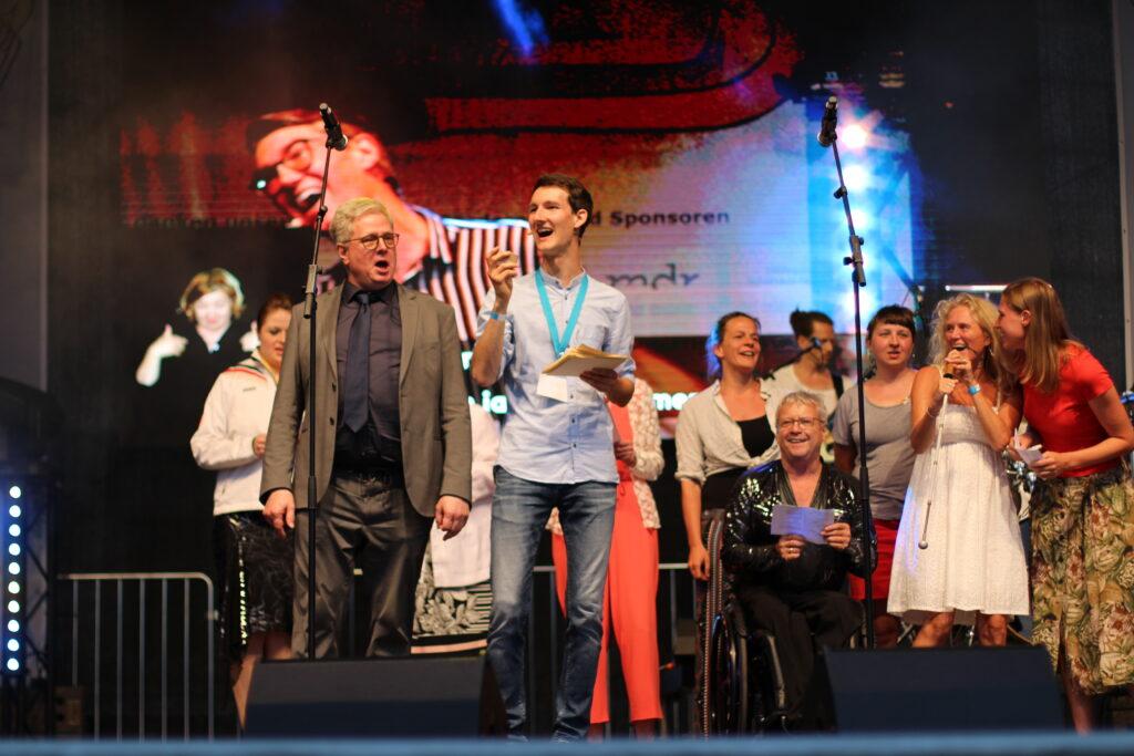 Viele Menschen auf einer großen Bühne. Im Vordergrund Prof. Dr. Thomas Kahlisch von der Deutschen Zentralbücherei für Blinde, neben ihm Moderator Florian Eib. Alle singen gemeinsam.