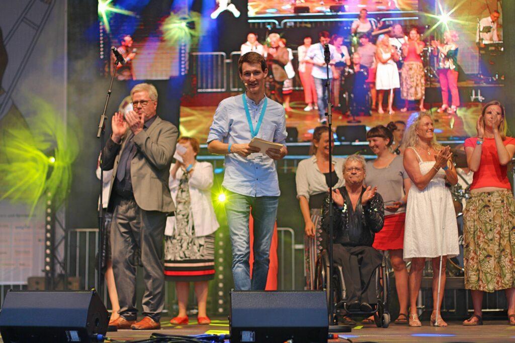 Im Vordergrund Moderator Florian Eib mit blauem Hemd und Moderationskarten in der Hand. Im Hintergrund mehrere Bühnengäste, die in die Hände klatschen.