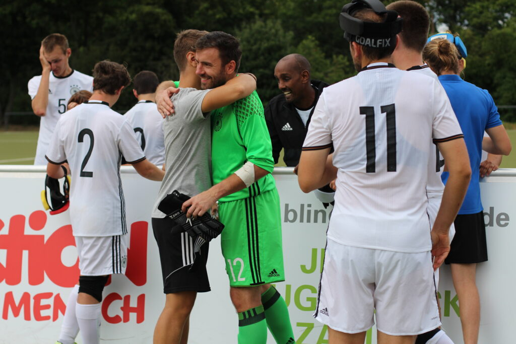 Torhüter Sebastian Themel und Guide Martin Mania umarmen sich nach dem Finaleinzug der Deutschen Blindenfußball-Nationalmannschaft beim Vier-Nationen-Turnier in Mönchengladbach.