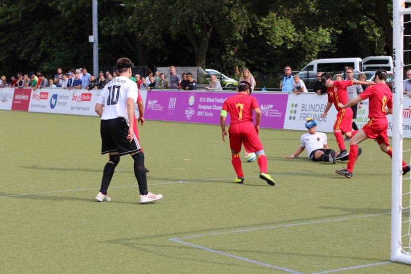Der deutsche Nationalspieler Taime Kuttig liegt auf dem Bode und wird von drei rumänischen Spielern umringt. Der Ball liegt frei in der Spielhälfte von Rumänien. Im Vordergrund Alexander Fangmann, der in Richtung des Balles läuft.