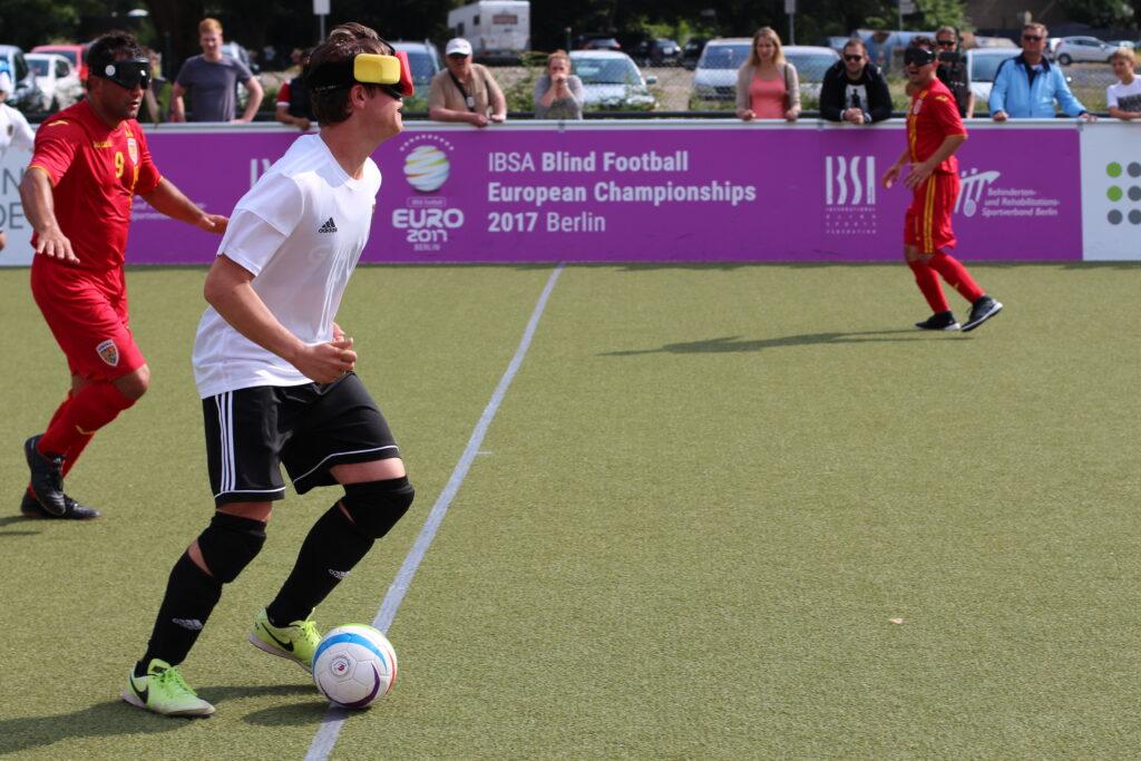 Nationalspieler Jonathan Tönsing treibt den Ball über die Mittellinie. Er wird von einem rumänischen Spieler verfolgt. Im Hintergrund sind zahlreiche Fans an der Spielfeldbande zu sehen.