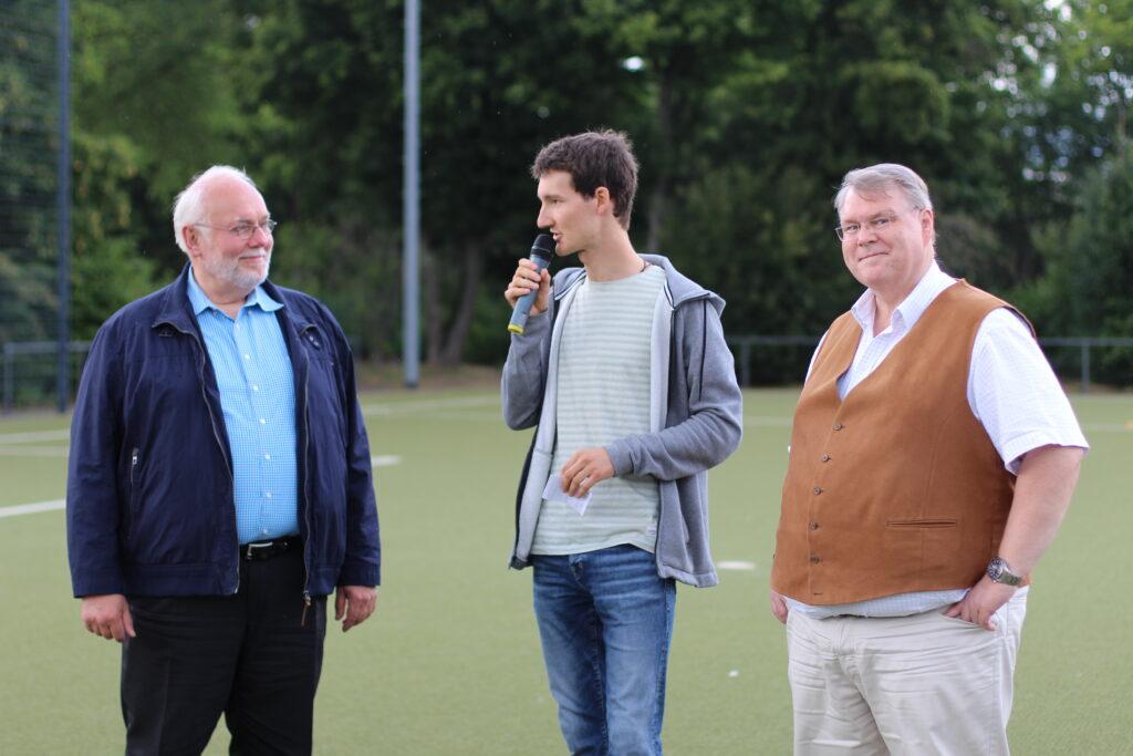 Sportreporter Florian Eib mit einem Mikrofon in der Hand. Neben ihm stehen Uwe Selenz und Torsten Bräuer. In Kürze werden die teilnehmenden Mannschaften beim Blindenfußball-Turnier geehrt.