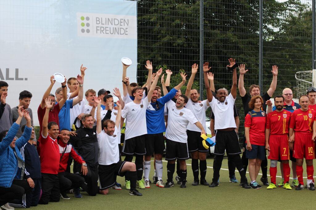 Die Deutschen Blindenfußball-Nationalmannschaft reißt die Arme zum Jubel nach oben. das Team steht mit allen anderen teilnehmenden Mannschaften des Vier-Nationen-Turniers bei der Siegerehrung.
