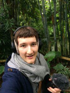 Selfie mit Mikrofon und Kopfhörern im Gondwana-Land im Leipziger Zoo. Im Hintergrund stehen großgewachsene grüne Pflanzen.