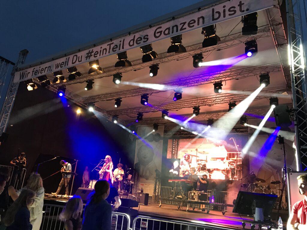 Auf einer großen Bühne spielt die Band DOTA. Die Sängerin DOTA steht mit Akustikgitarre am Mikrofon. Im Hintergrund spielt die Band bestehend aus Schlagzeuger, Pianist und Gitarrist.