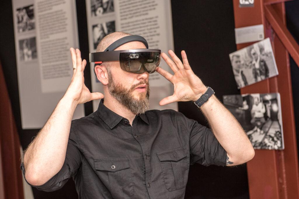 Ein Mann mit Glatze und Vollbart trägt eine BLINDSPOTTER MR Brille. Er hat beide Hände neben den Kopf gehoben und deutet an, dass er etwas hört.