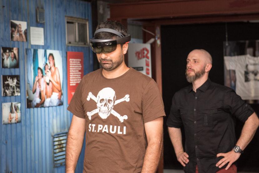 Blindenfußballer Serdal Celebi trägt eine BLINDSPOTTER MR Brille und läuft durch eine Ausstellung mit Exponaten an der Wand.