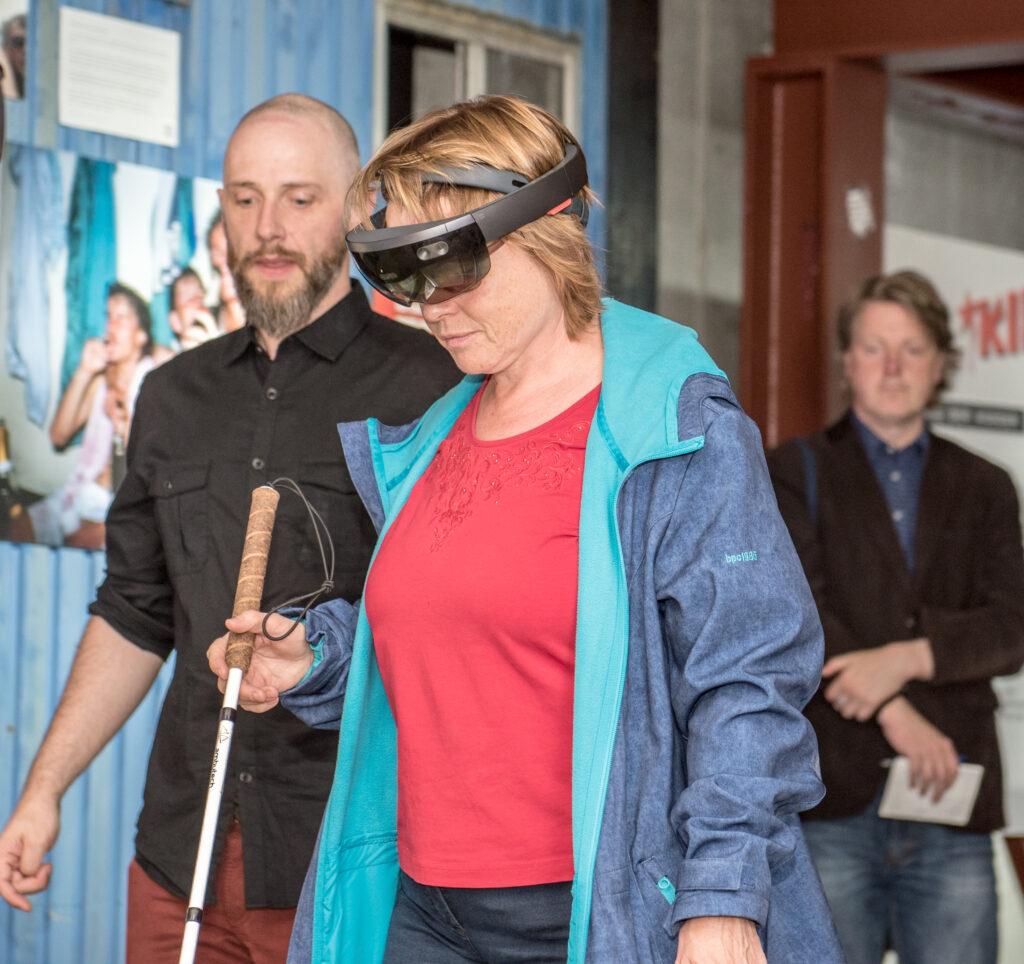 Eine sehbehinderte Person geht mit einem Blindenstock durch ein Ausstellungsgebäude. Auf dem Kopf trägt sie eine Brille, die eine automatische Wegbeschreibung und zusätzliche Beschreibungen von Exponaten abspielt.