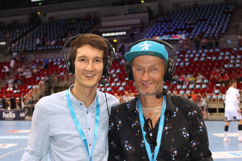 Sprecher für Audiodeskription Wolf Schmidt (r.) und Florian Eib (l.) im Düsseldorfer ISS-Dome. Sie stehen am Spielfeldrand des Handballfeldes. Im Hintergrund Spieler des THW Kiel beim Warmmachen.