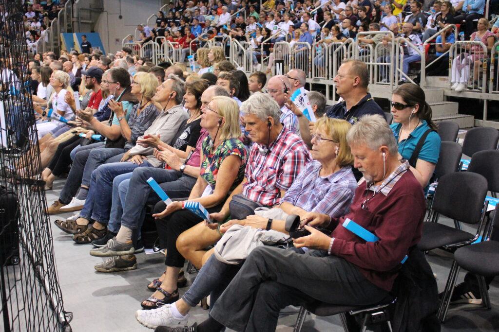 Gäste der Audiodeskription im ISS DOME Düsseldorf. In zwei Reihen sitzen sehbehinderte und blinde Menschen mit ihren Begleitpersonen am Spielfeldrand. Sie haben Kopfhörer auf und verfolgen das Spiel durch eine Spielbeschreibung von Wolf Schmidt und Florian Eib.
