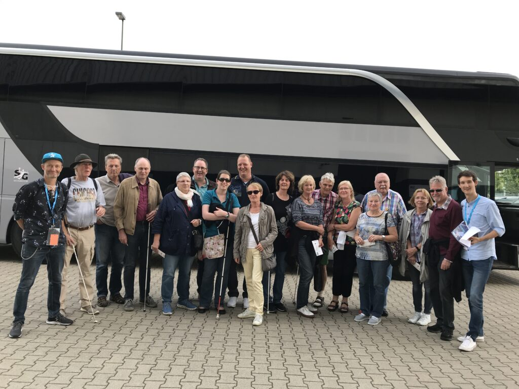Gruppenfoto vor dem ISS DOME. Die Gäste der Audiodeskription und die Sprecher für Audiodeskription Florian Eib und Wolf Schmidt. Einige der Gäste haben Blindenstöcke dabei. Im Hintergrund der Mannschaftsbus der SG Flensburg-Handewitt.