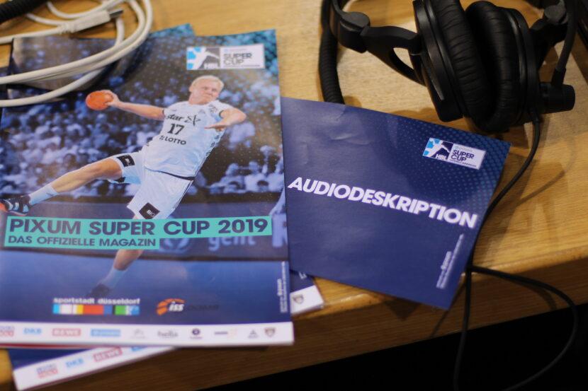 Auf dem Pressetisch liegt das Programmheft des Pixum Supercup 2019. Auf dem Cover der Kieler Patrick Wienczek beim Sprungwurf. Im Heft steckt der Reservierungszettel für den Presseplatz. Darauf steht Audiodeskription. Auf dem Tisch liegen auch Kabel und ein Headset.