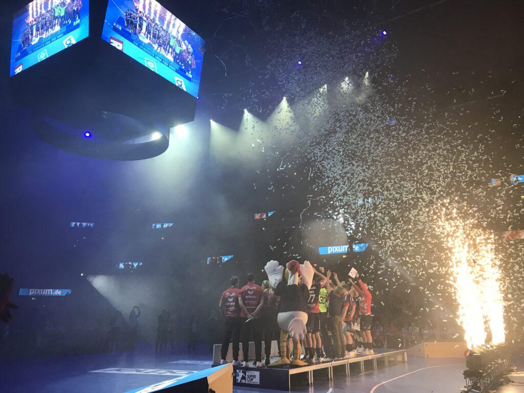 Jubel im abgedunkelten ISS DOME Düsseldorf. Der Gewinner des Pixum Supercup 2019 die SG Flensburg-Handewitt reckt den Pokal in die Höhe. Im Hintergrund fliegt Konfetti in die Luft. Feuerfontänen erhellen den Raum.