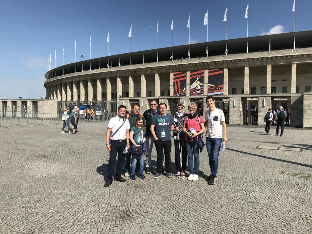 Gruppenfoto vor dem Berliner Olympiastadion. Sehbehinderte und blinde Gäste gemeinsam mit den Sportreportern. Es strahlt die Sonne und alle lachen in die Kamera.
