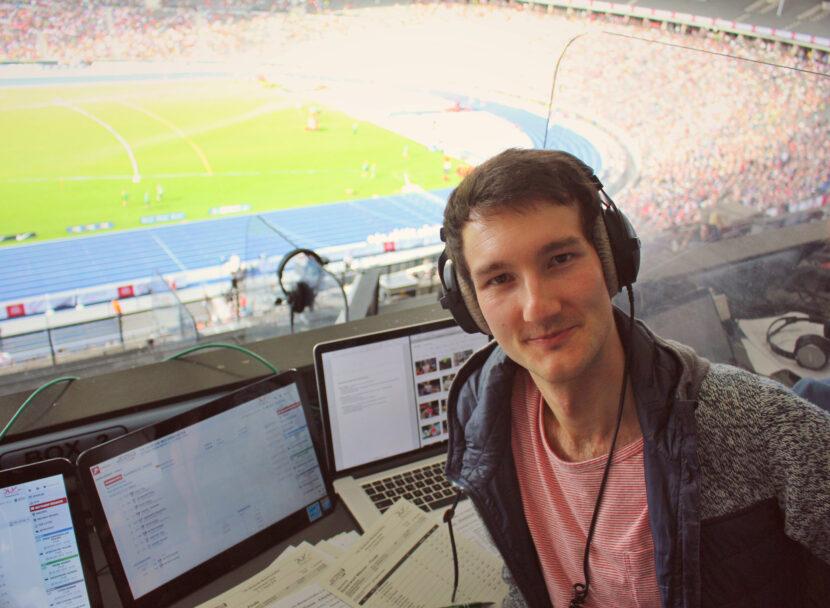 Sportreporter Florian Eib im Berliner Olympiastadion. Das Stadion im Hintergrund ist gut gefüllt. Florian Eib schaut in die Kamera. Er sitzt an seinem Arbeitsplatz, auf dem zahlreiche Blätter und Monitore stehen.