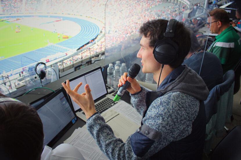Sportreporter Florian Eib sitzt auf seinem Reporterplatz im Olympiastadion Berlin und spricht in ein Mikrofon. Er spricht die Audiodeskription für sehbehinderte und blinde Menschen bei dieser Veranstaltung.