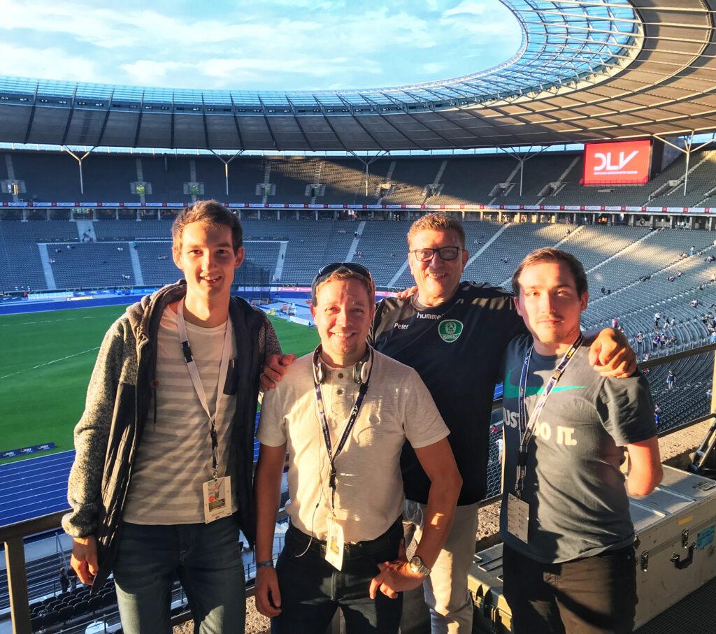 Gruppenfoto im Olympiastadion Berlin. Das Team um Sportreporter Florian Eib, welches für die Deutschen Leichtathletikmeisterschaften 2019 die Audiodeskription erstellt hat. Es ist Abend nach dem ersten Arbeitstag. Im Hintergrund geht langsam die Sonne unter.