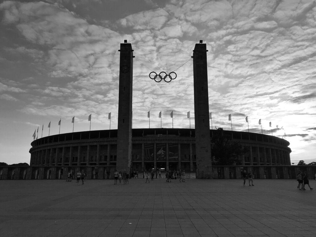 Ein lauer Abend verabschiedet die Gäste nach den Deutschen Leichtathletik-Meisterschaften in Berlin. Auf dem Schwarz-Weiß-Foto außerhalb des Olympiastadions sind die Olympischen Ringe hoch über dem Eingangsportal deutlich zu erkennen.