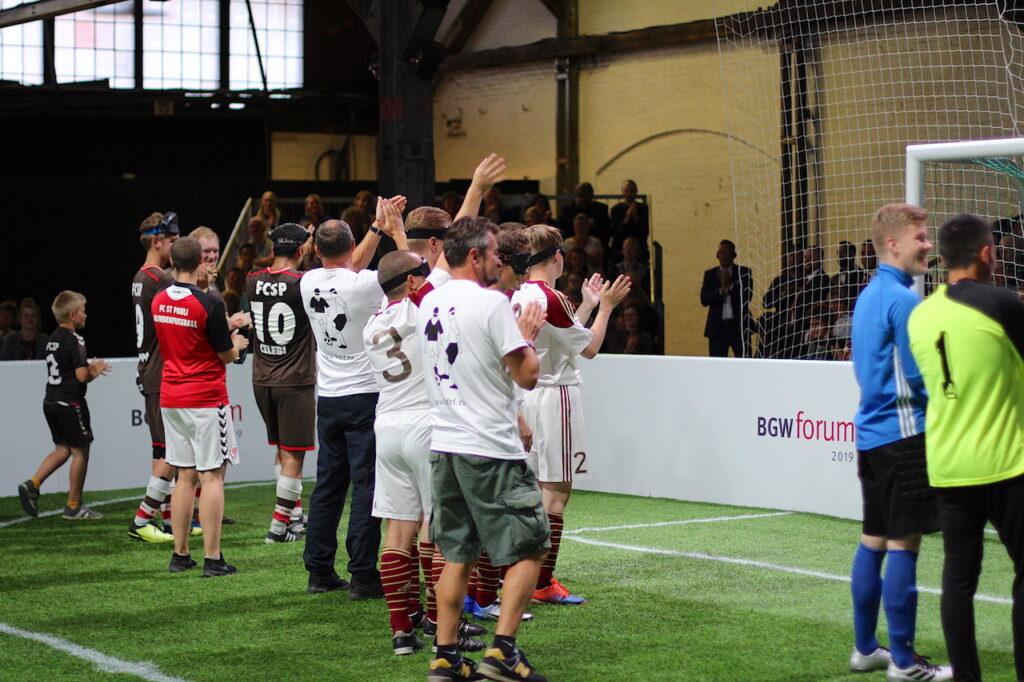 Die Blindenfußballmannschaften von Stern Moskau und FC St. Pauli auf dem Kunstrasen des Spielfeldes. Die Spieler und Trainer applaudieren in Richtung der gut gefüllten Zuschauerränge.