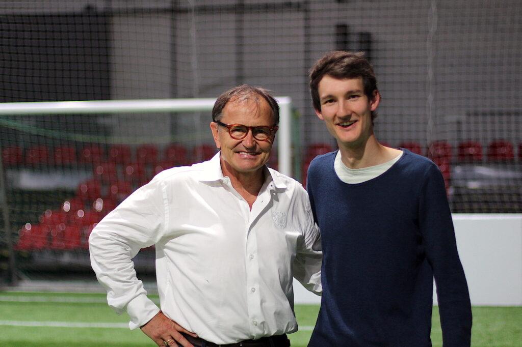 Der Technische Direktor des FC St. Pauli Ewald Lienen und Sportreporter Florian Eib stehen gemeinsam auf dem Spielfeld eines Blindenfußballfeldes und lachen in die Kamera.