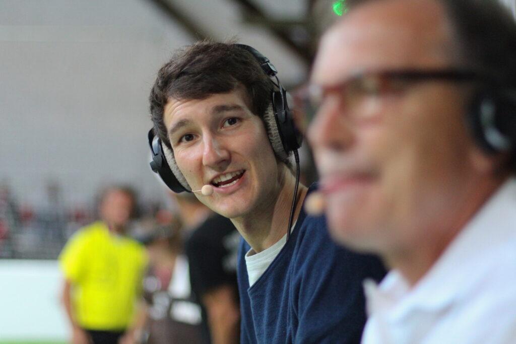 Sportreporter Florian Eib steht seitlich am Rand eines Blindenfußballfeldes und schaut lächelnd in die Kamera. Er hat ein Headset und und trägt einen dunkelblauen Pullover.