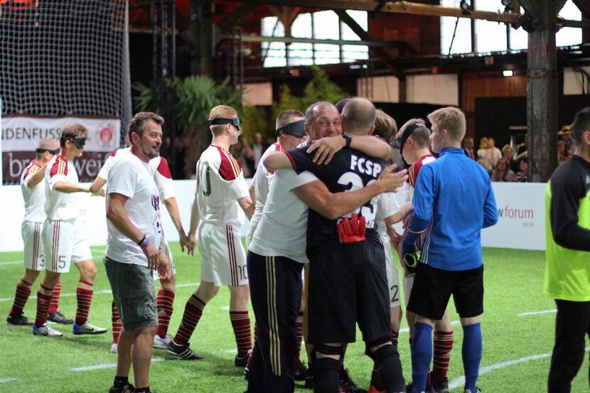 Trainer und Spieler der Blindenfußballmannschaften vom FC St. Pauli und Stern Moskau nehmen sich nach einem Freundschaftsspiel in den Arm. Sie stehen auf einem Blindenfußballspielfeld.