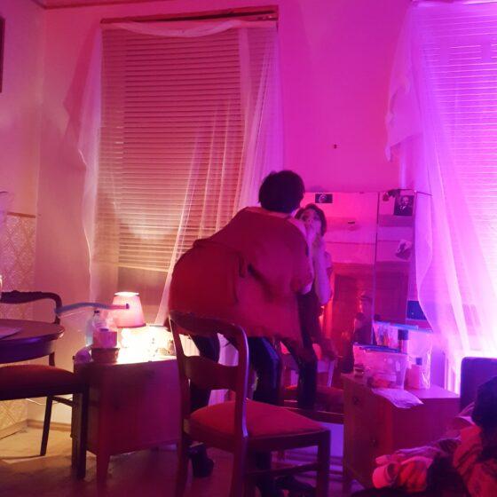 Ein Raum im pinken Licht. Die Fenster sind verhangen. Eine Frau in knapper Kleidung schminkt sich vor einem Spiegel die Lippen rot.