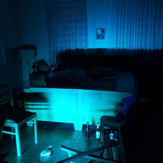 Ein abgedunkelter Raum mit einem Ehebett. Davor liegt einumgefallener Tisch, Bierflaschen stehen auf dem Boden.
