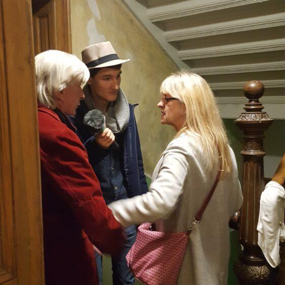 Reporter Florian Eib interviewt zwei Gäste des Abends. Sie befinden sich im Treppenhaus.