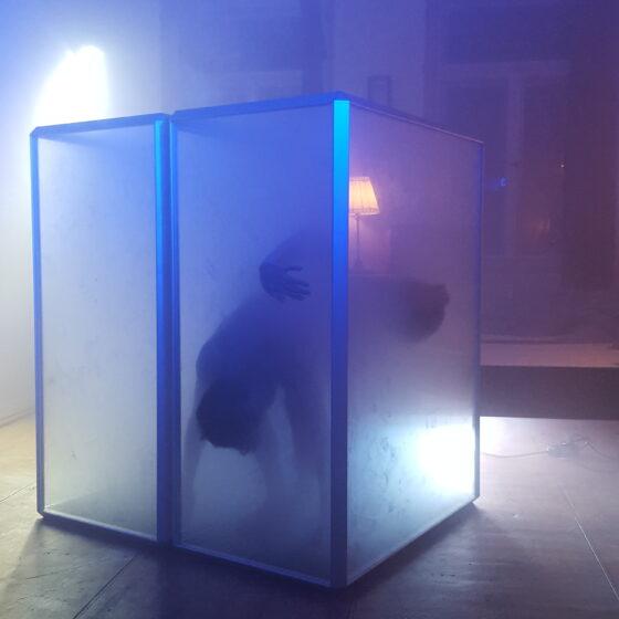 In einem vernebelten Raum stehen zwei Kasten aus Kunststoff in denen zwei Menschen gefangen sind.