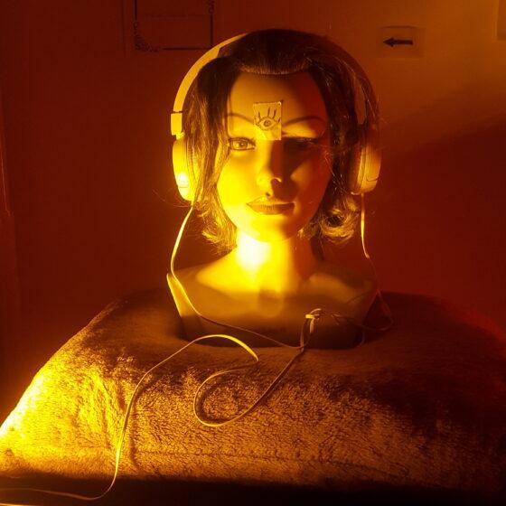 Ein Frisierkopf steht auf einem Kissen und hat Kopfhörer auf. Der der kleine Raum ist in oranges Licht getaucht. Vor dem Frisierkopf liegt eine Querflöte.